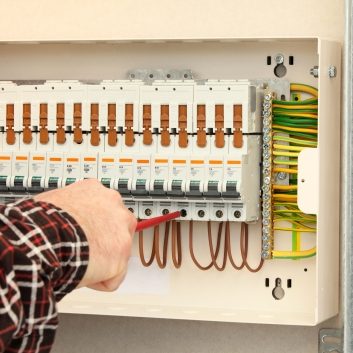 electrician-working-at-a-fuse-box-183816841-5877c5075f9b584db3490d1a
