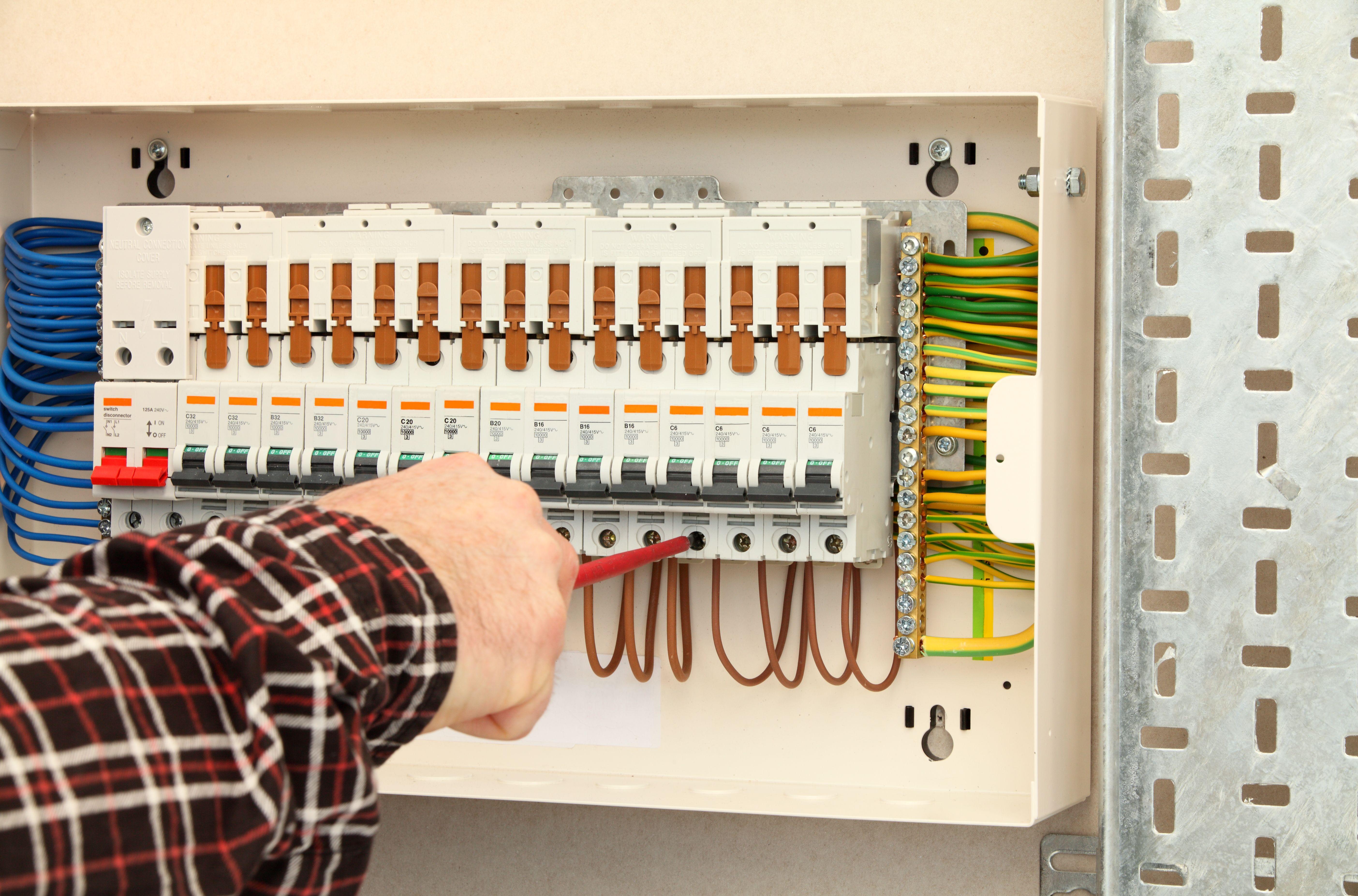 electrician-working-at-a-fuse-box-183816841-5877c5075f9b584db3490d1a